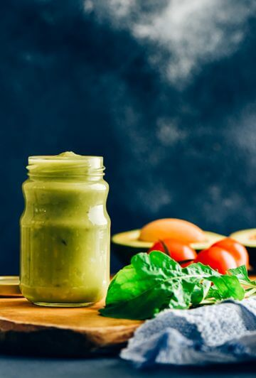 Avocado dressing in a glass jar on a wooden board