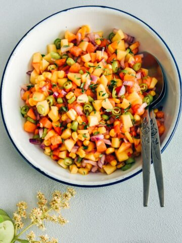 Corn peach salsa in a white bowl with spoons