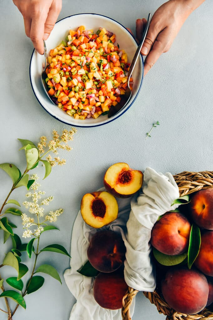 Hands stirring fresh corn peach salsa in a white bowl