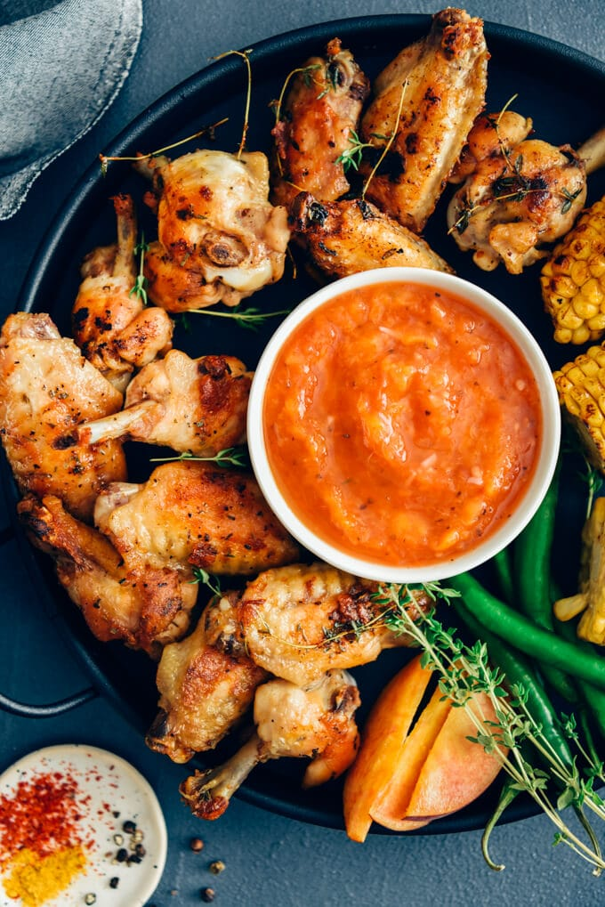 Sugar free bbq sauce with peaches served with chicken wings on a black pan
