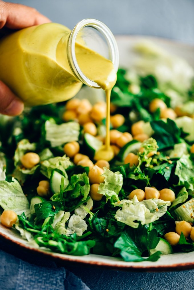 Pouring turmeric tahini dressing over a bowl of green salad with chickpeas.