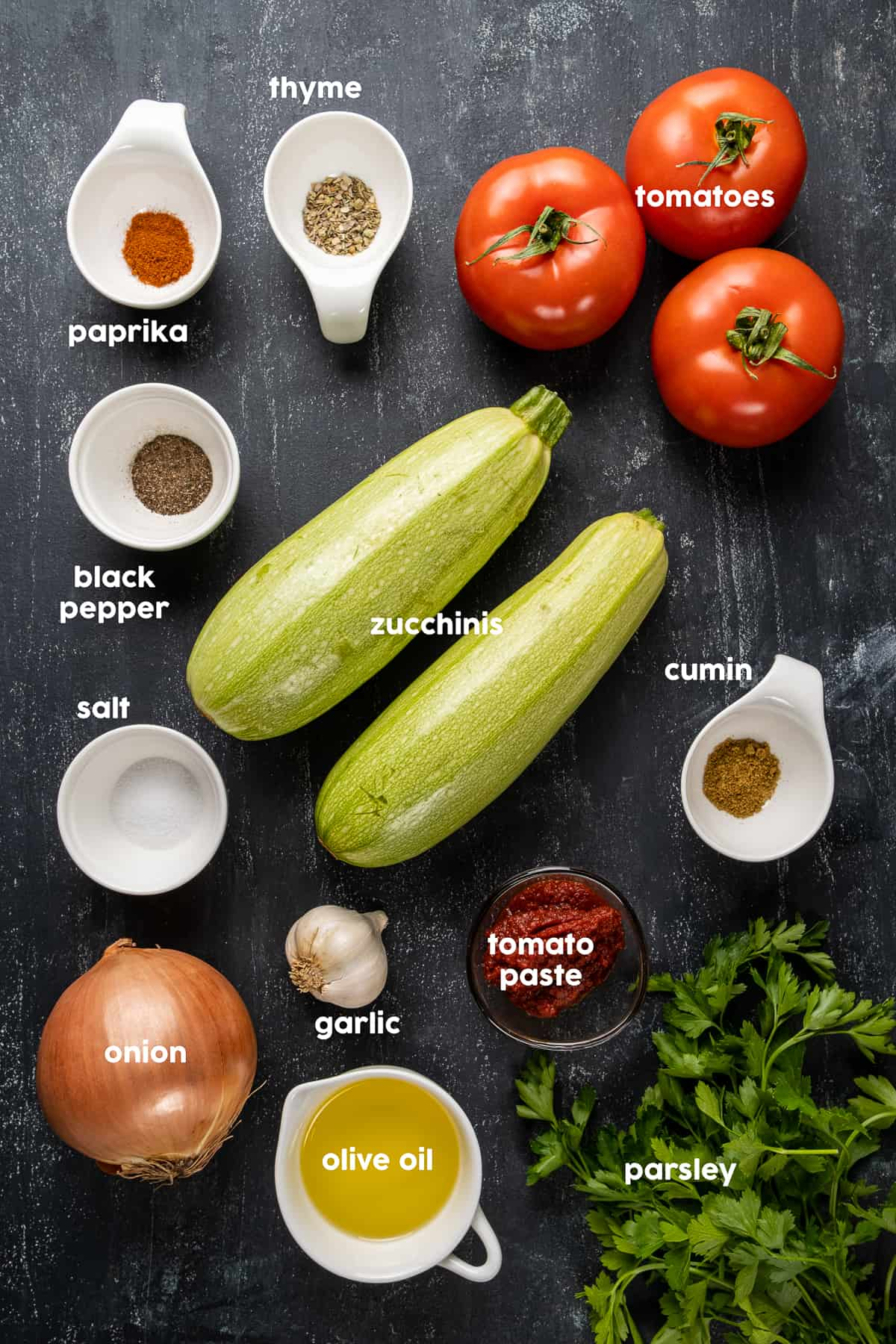 Zucchini, tomatoes, spices, garlic, onion, olive oil, tomato paste, parsley on a dark background.