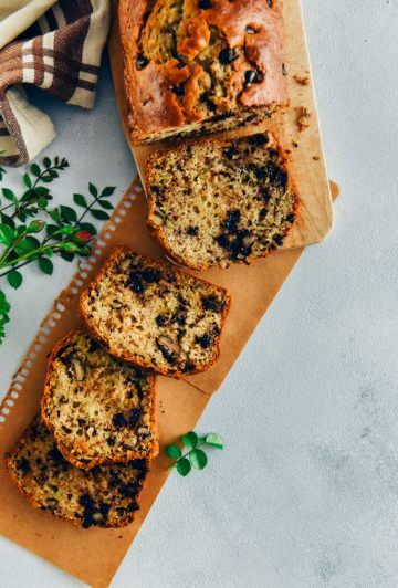 Chocolate chip zucchini bread with walnuts sliced on a wooden board and brown paper on a grey background