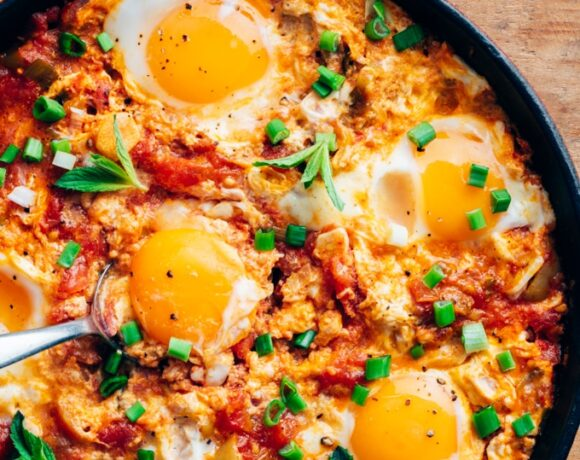 Turkish menemen recipe with eggs and tomatoes in a pan.