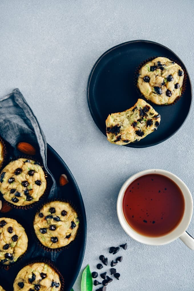 Chocolate chip zucchini muffins in a black tray and in a small black plate, a cup of tea, green leaves and chocolate chips.