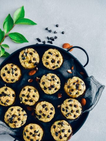 Zucchini chocolate chip muffins served in a black tray with a grey linen