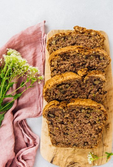 best vegan zucchini bread slices on a wooden board with flowers