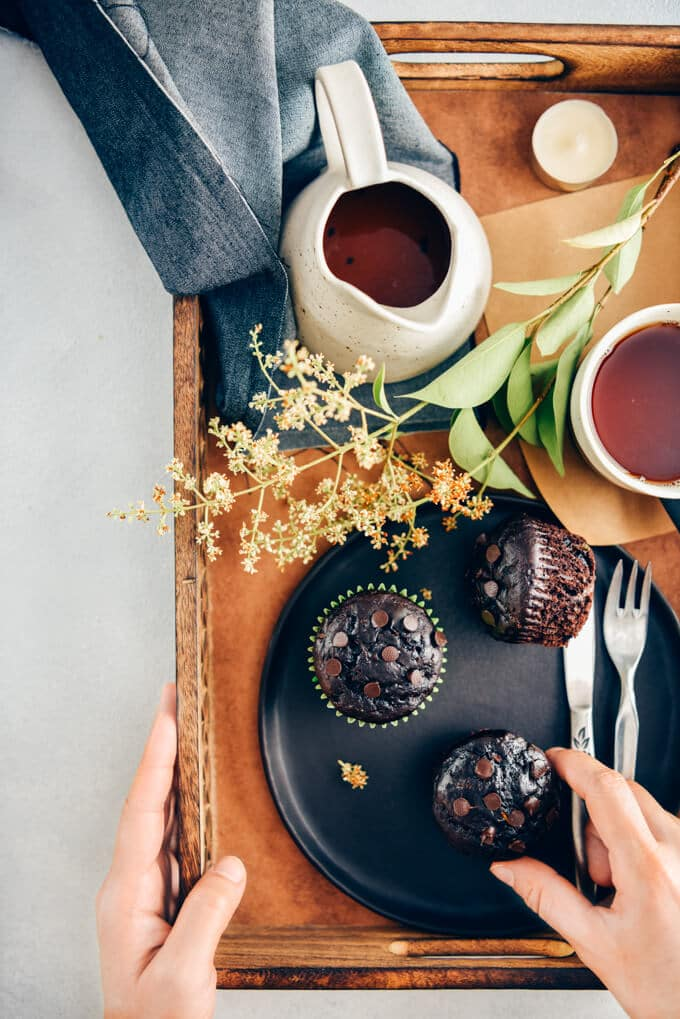 Person holding a wooden tray with healthy chocolate zucchini muffins on a black plate and tea