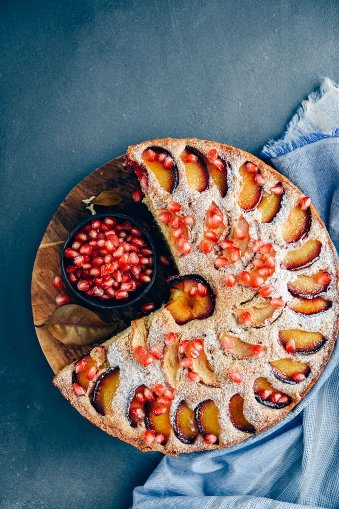 Apple plum cake on a wooden stand accompanied by a small bowl of pomegranate arils.