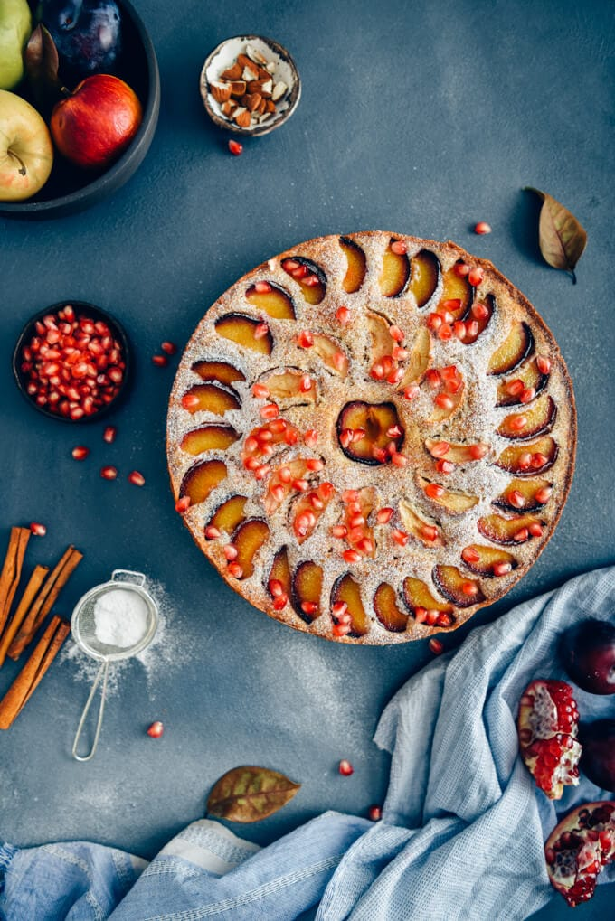 Apple plum cake on a dark backdrop accompanied by almonds, cinnamon sticks, pomegranate arils, apples and plums.