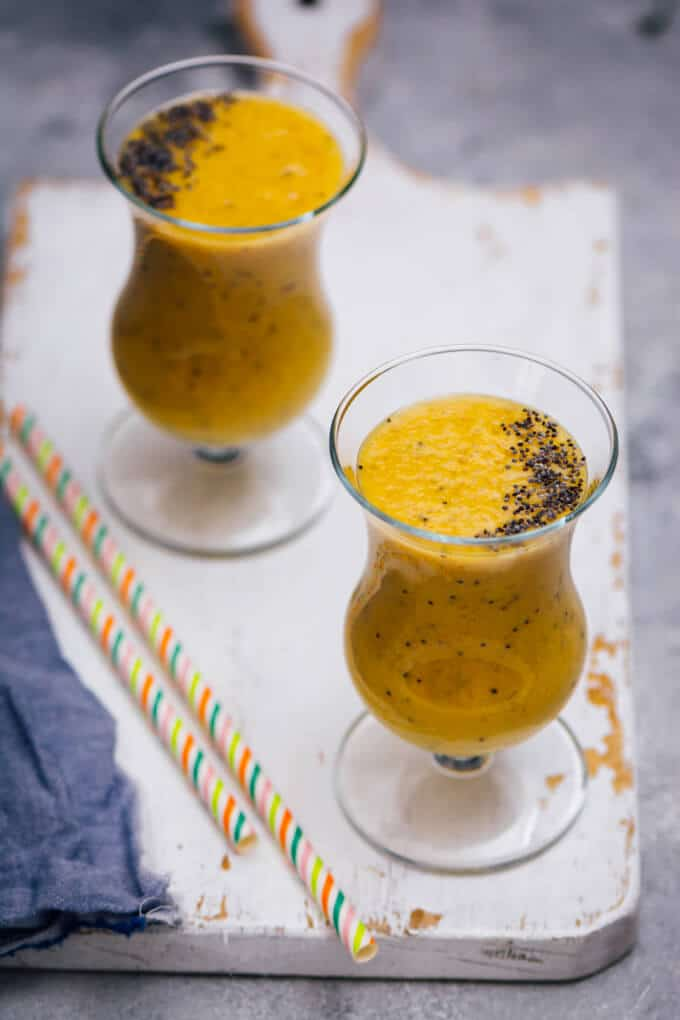 Two glasses of turmeric golden milk smoothie topped with poppy seeds photographed with two straws on the side