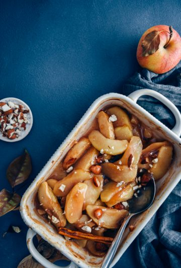 Cinnamon baked apple slices in a baking pan accompanied by apples and almonds.