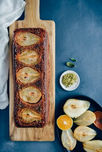Pear bread on a wooden board accompanied by caramelized pears and a wedge of orange in an iron pan on the side.