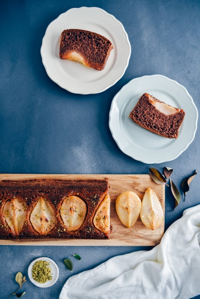 Pear loaf cake sliced on a wooden board accompanied by two plates, a small bowl of pistachio.