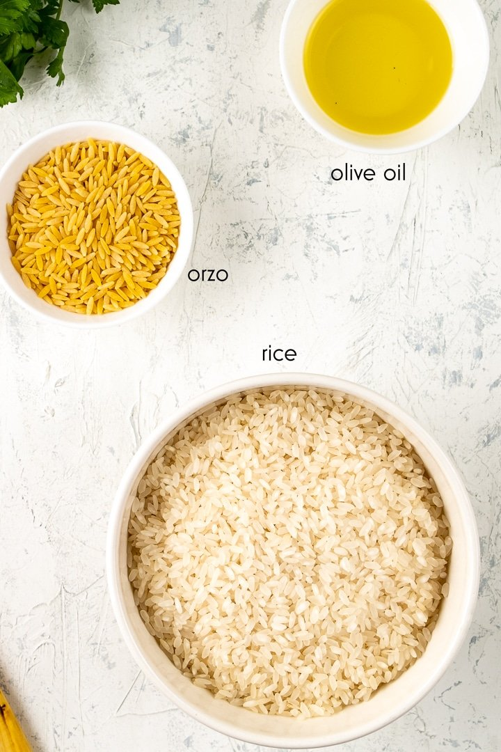 Orzo, rice and olive oil are in separate bowls on a white background.