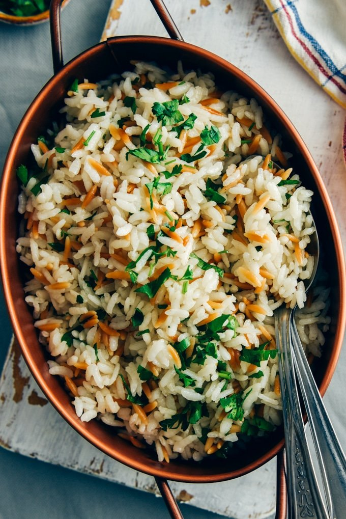 Rice pilaf with orzo served in a copper pan with two spoons on the side.