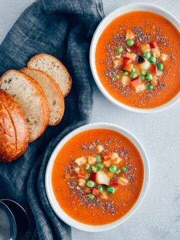 Vegan tomato soup served in two white bowls accompanied by bread rolls, roasted garlic, croutons and peas.