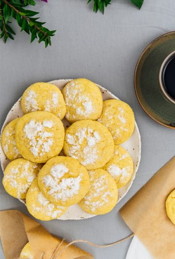 Lemon crinkle cookies on a white plate with a cup of coffee on the side.