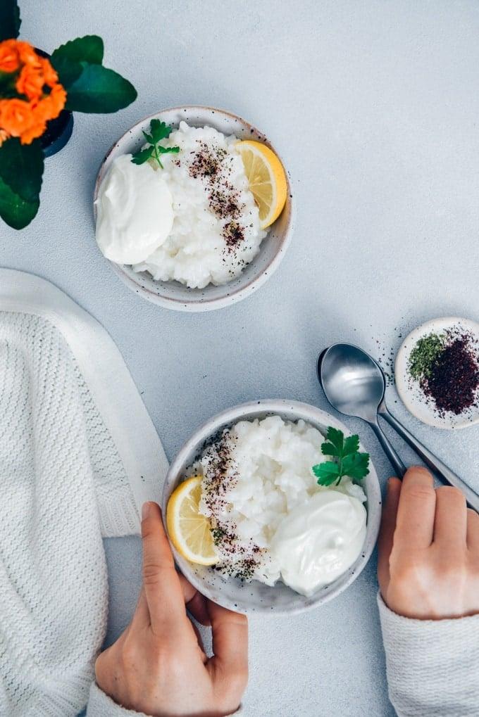 Woman eating savory rice porridge garnished with yogurt, lemon wedges, sumac and dried mint.