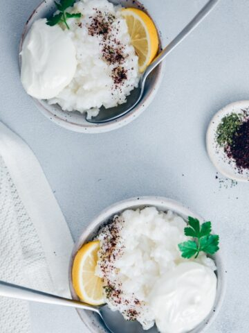 Savory rice porridge in two ceramic bowls garnished with yogurt, sumac, dried mint and lemon wedges photographed on a grey background.