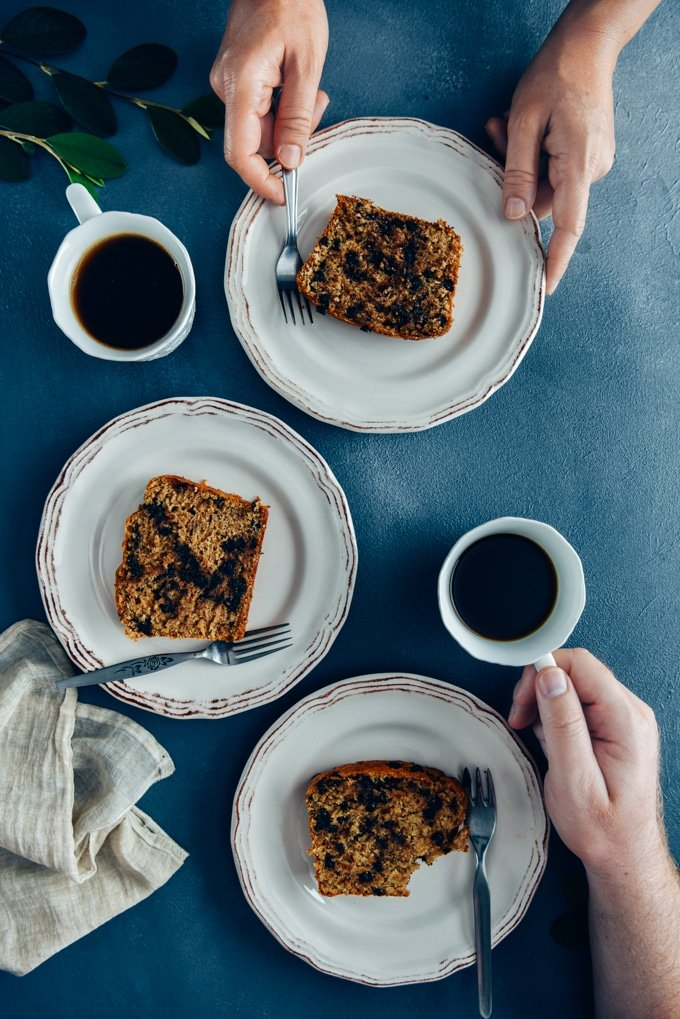 Two people having breakfast with chocolate chip banana bread served on white plates and tea.