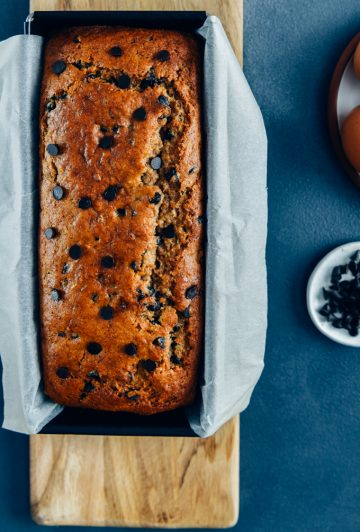 Chocolate chip banana bread in a baking pan on a wooden cutting board.