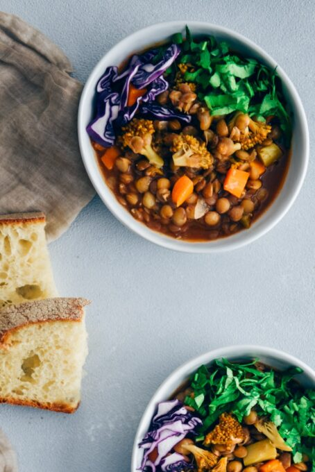 Vegan lentil stew with broccoli and carrot garnished with shredded red cabbage and chopped parsley served in white bowls.