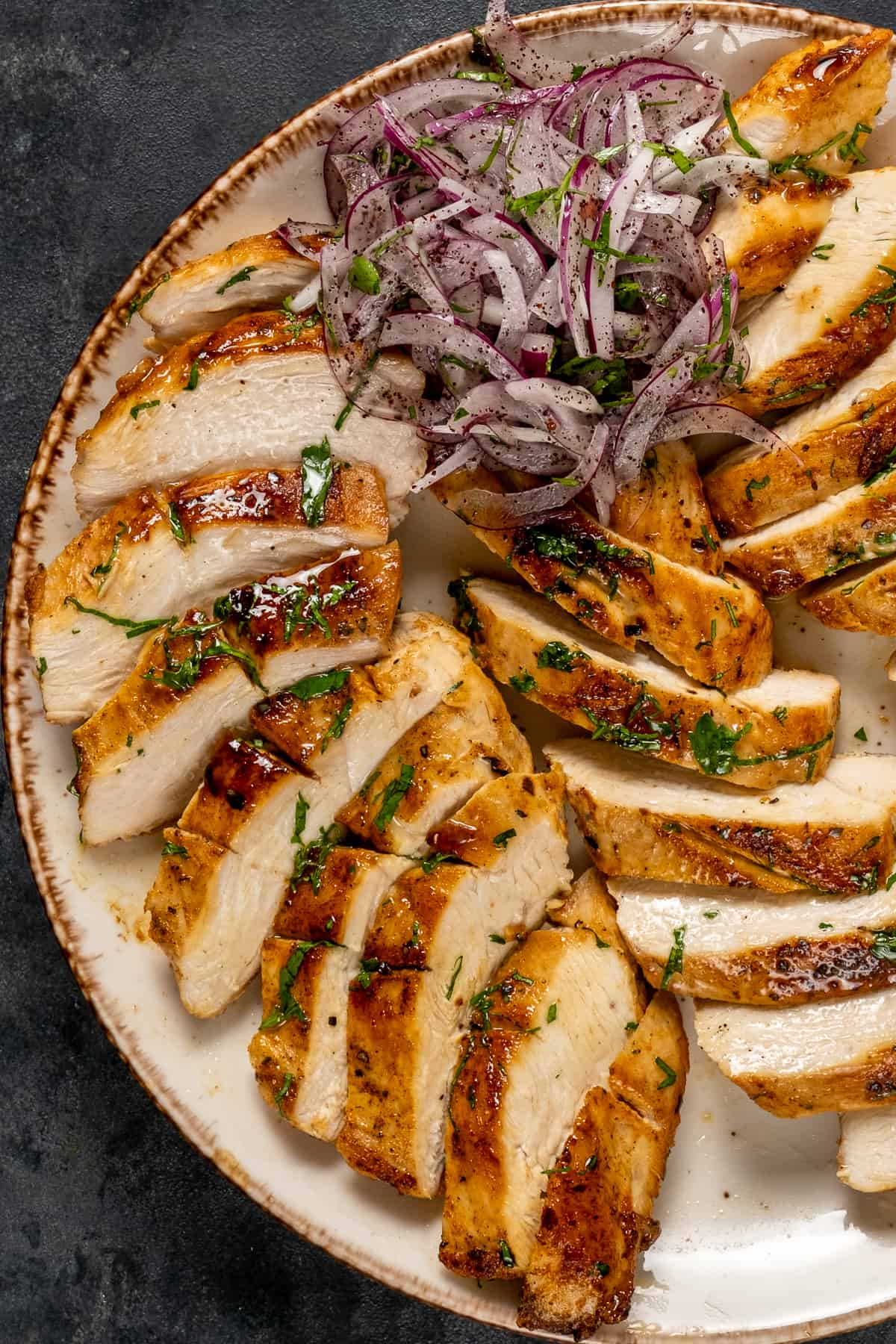 Cast iron pan cooked chicken breasts sliced and served with sumac onions on a plate.