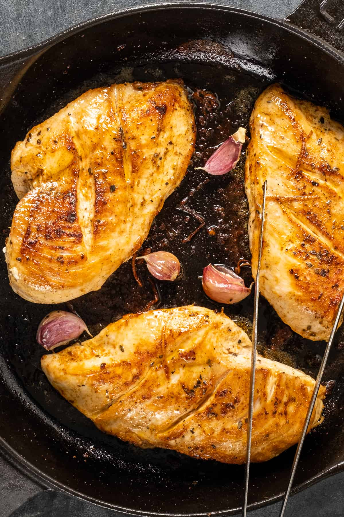 Golden cooked chicken breasts and garlic cloves with their skin in a cast iron pan.