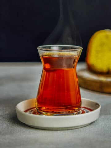 Hot Turkish tea in its traditional tea glass and saucer.