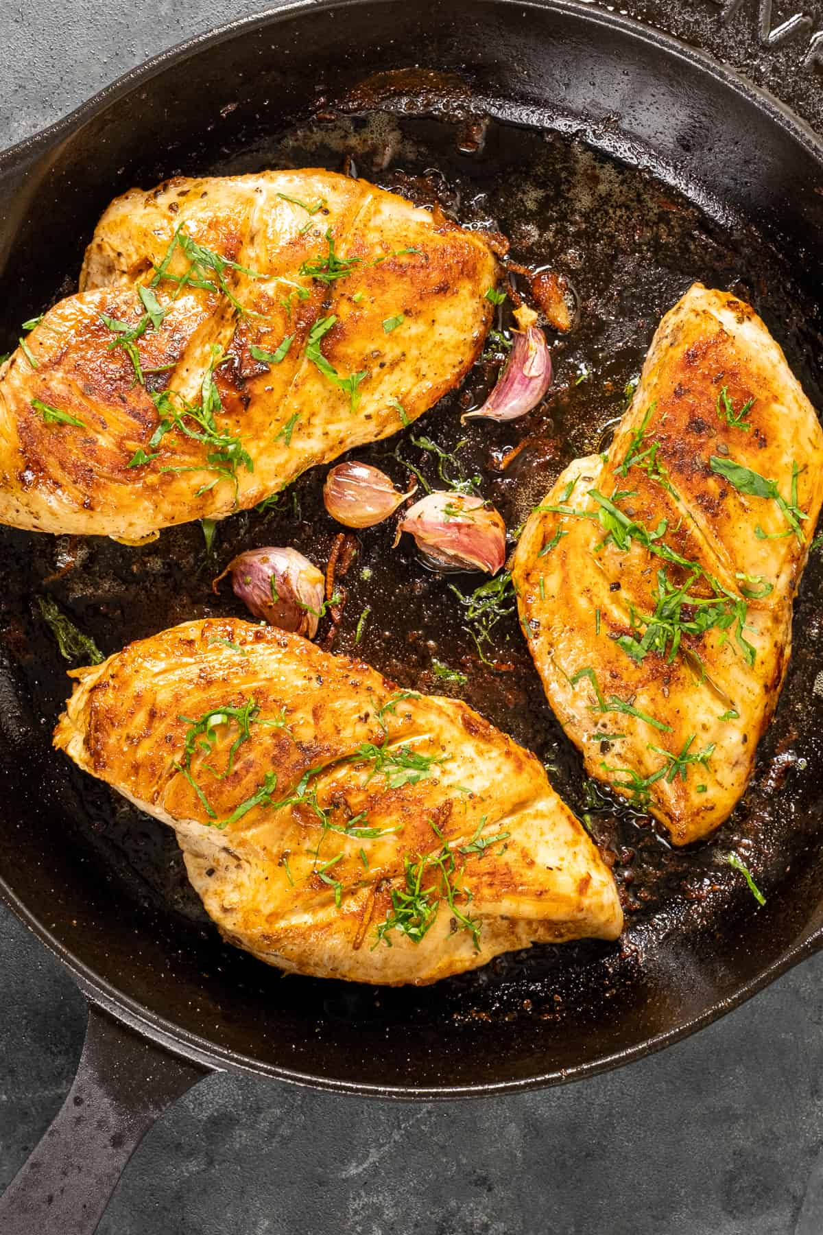 Cooked chicken breasts garnished with chopped parsley and garlic cloves in a cast iron skillet.