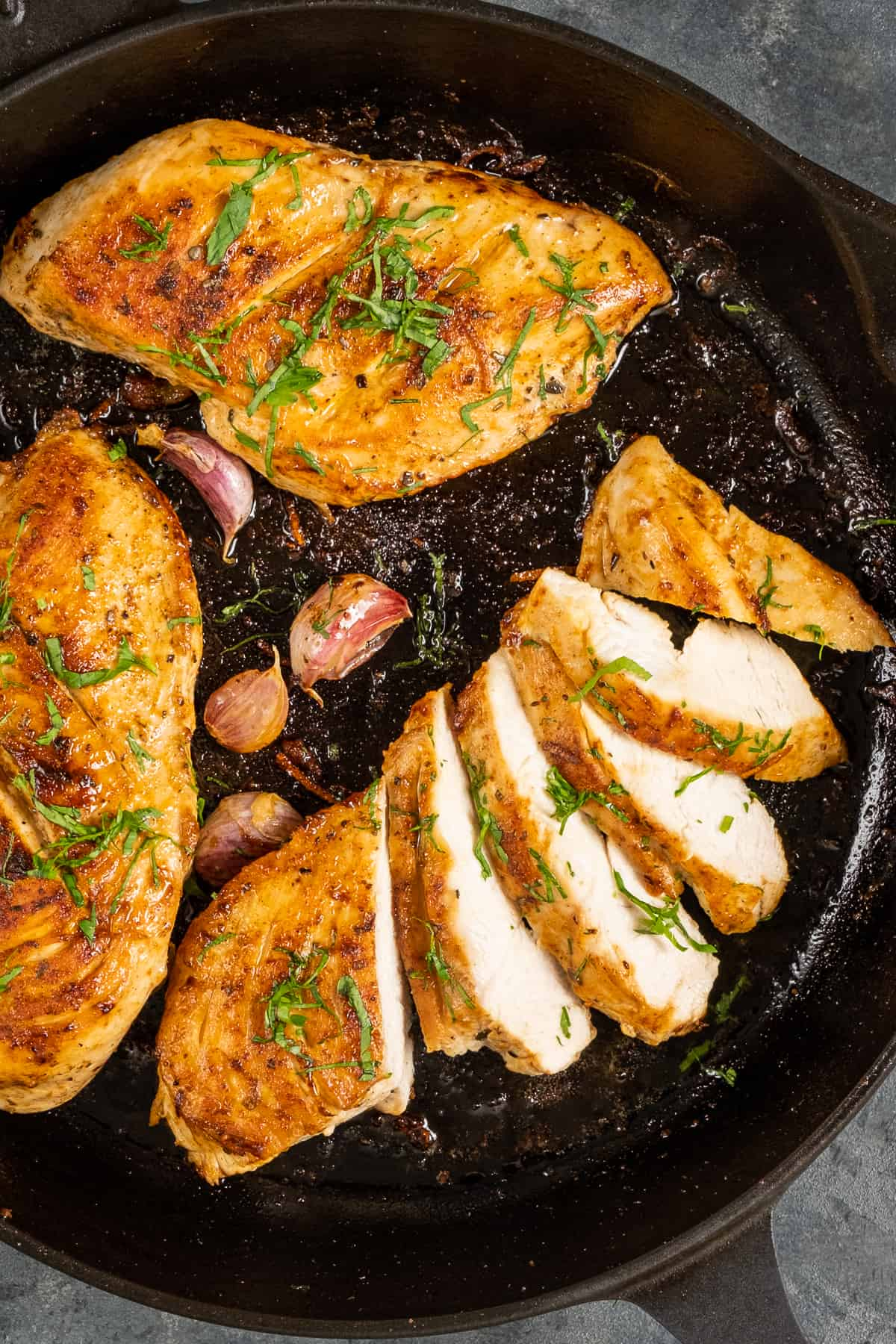 Three pieces golden brown chicken breasts, one sliced, in a cast iron pan garnished with chopped parsley and garlic cloves on the side.