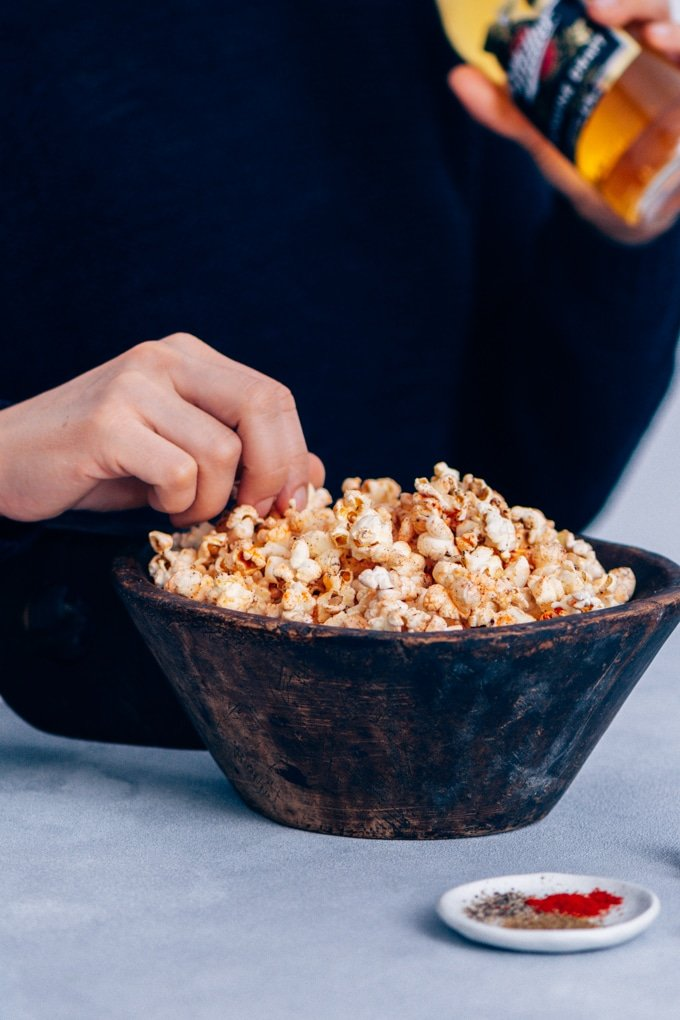 Woman eating spicy popcorn in a wooden bowl for easy game day snacks