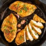 Cooked chicken breasts in a cast iron pan, one of them is sliced, garnished with parsley, accompanied by unpeeled garlic cloves.