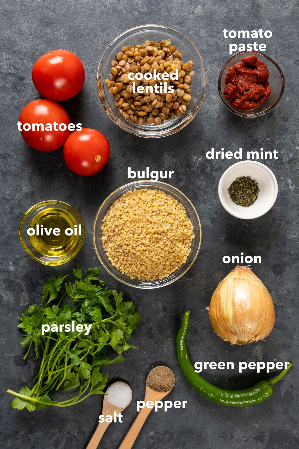 Bulgur in a glass bowl, cooked green lentils in a glass bowl, tomato paste, olive oil and dried mint in small bowls, salt and pepper in wooden spoons, onion, green pepper, parsley and tomatoes on a dark background.