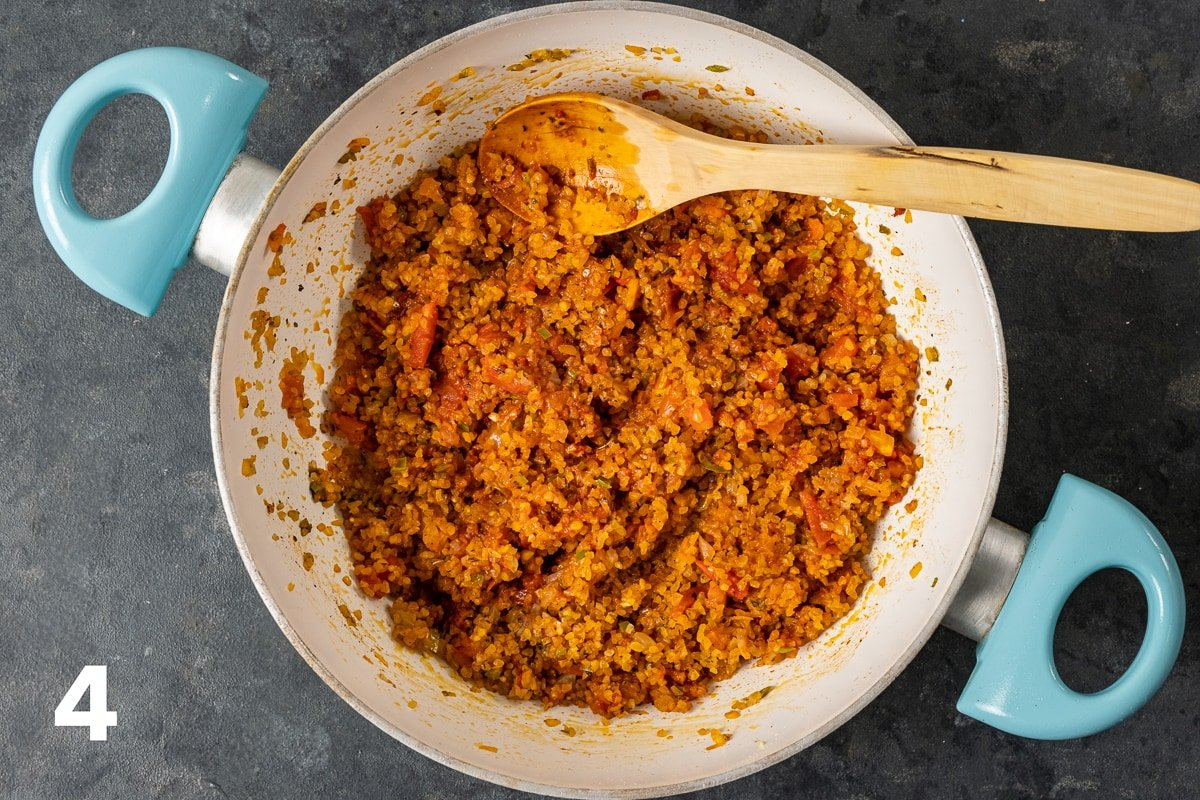 Bulgur mixed with cooked onions, peppers, tomatoes, tomato paste and spices in a white pan and a wooden spoon inside it.
