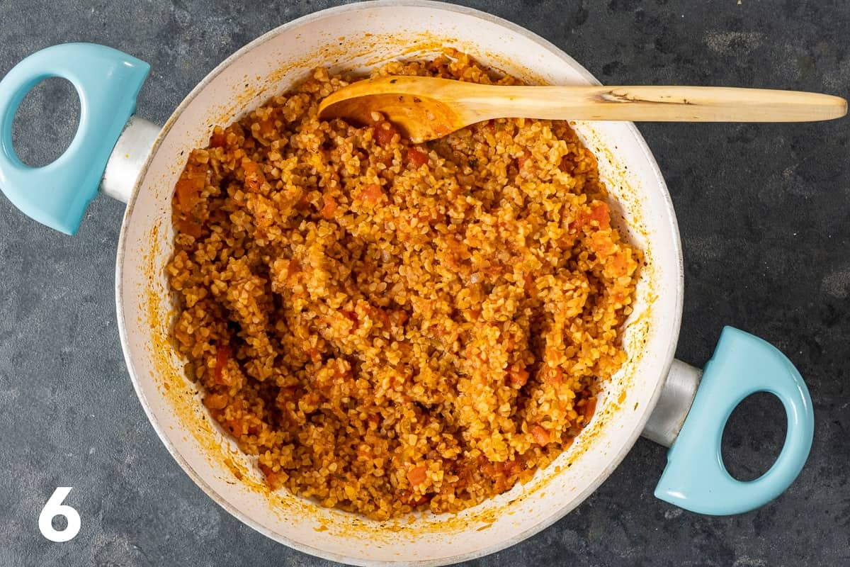 Cooked tomato bulgur pilaf in a pan with a wooden spoon inside it.
