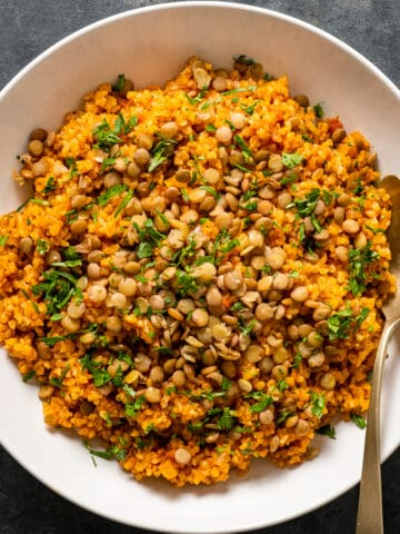 Spicy tomato bulgur pilaf topped with green lentils and parsley in a white bowl with a spoon inside it.