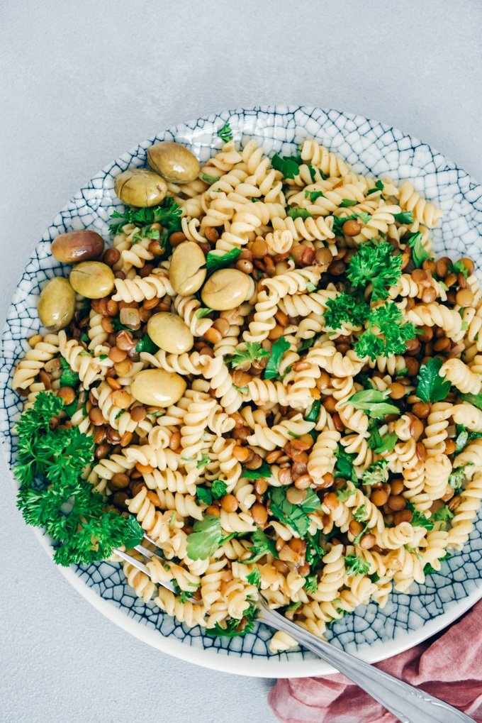 Pasta with vegan bolognese sauce, parsley and green olives served a salad.