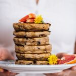 Woman holding a stack of egg free pancakes with chocolate chips on a plate with flowers and grapefruit wedges.