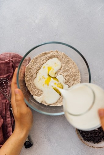 Woman pouring milk into the dry ingredients mixture in a glass bowl to make fluffy egg free pancakes.
