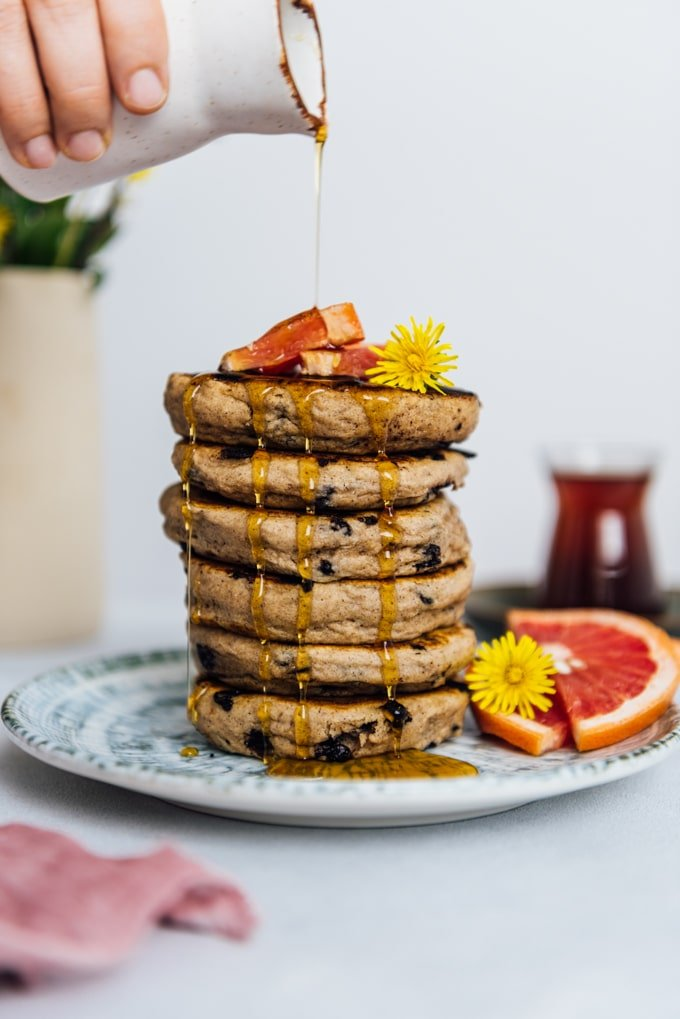 Woman pouring maple syrup over a stack of pancakes that are made without eggs. Spring flowers, grapefruit wedges, Turkish tea accompany.