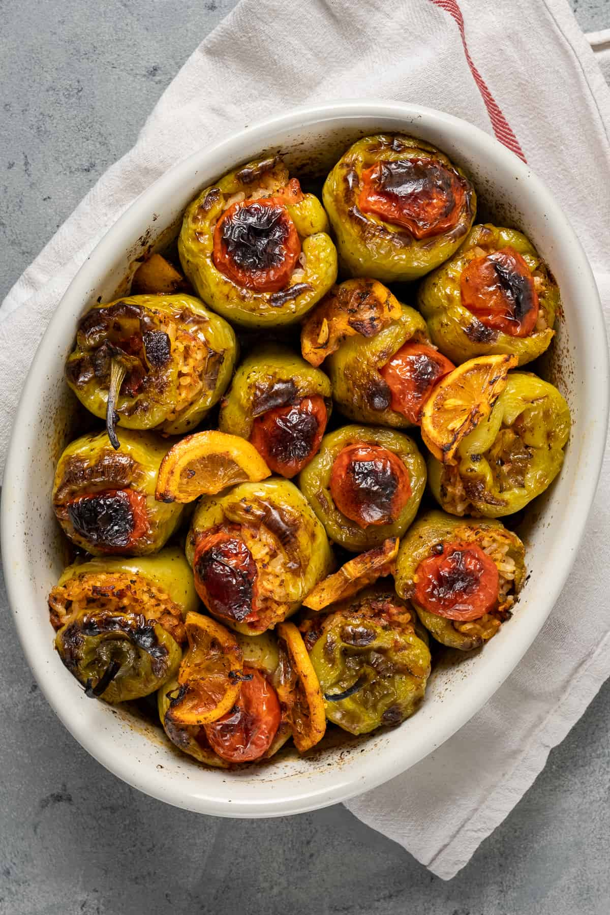 Baked rice stuffed green peppers in a white oval baking pan.