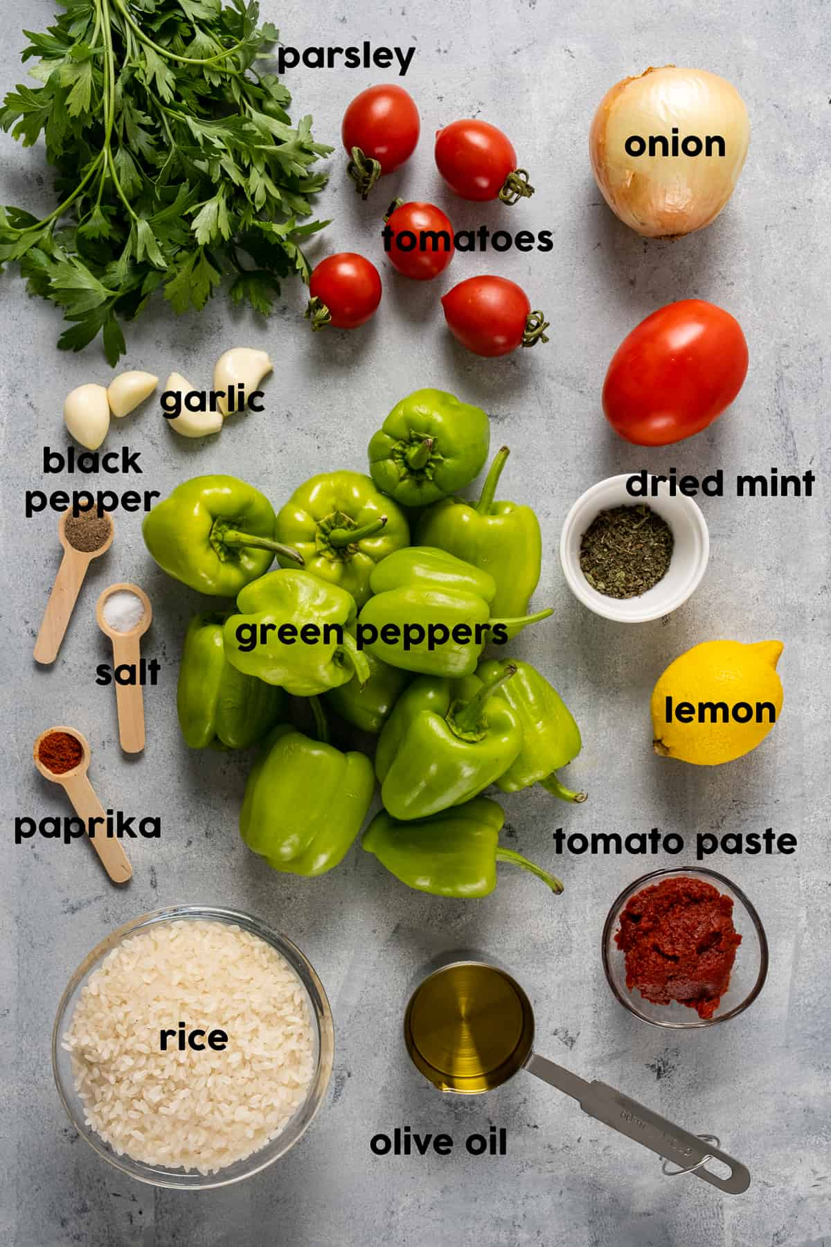 Turkish peppers, tomatoes, garlic, parsley, tomato paste, rice, spices, lemon, onion and olive oil on a light background.