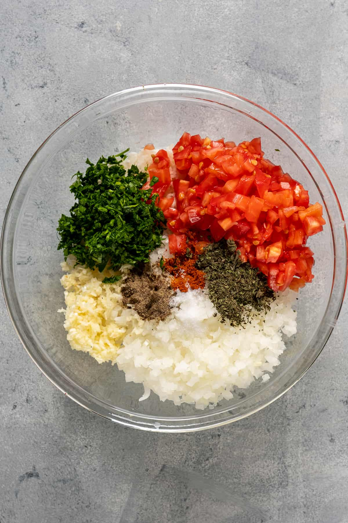 Rice, chopped garlic, onion, tomatoes, parsley and spices in a glass mixing bowl.