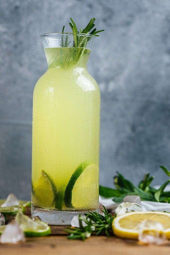 Vodka lemonade flavored with rosemary in a bottle garnished with lime slices.