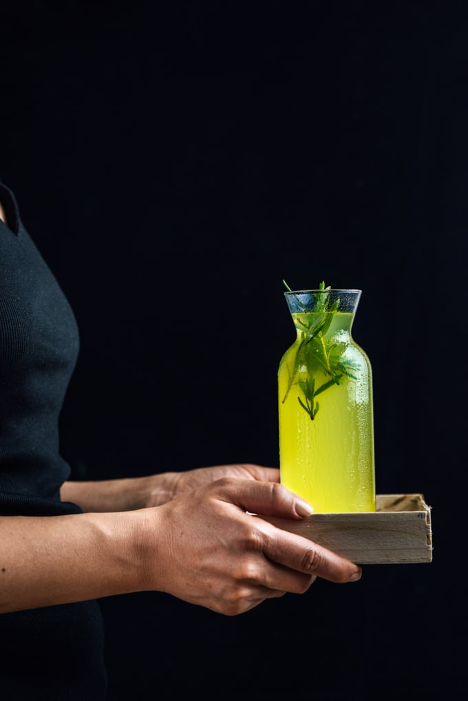 Woman holding a bottle of vodka lemon cocktail