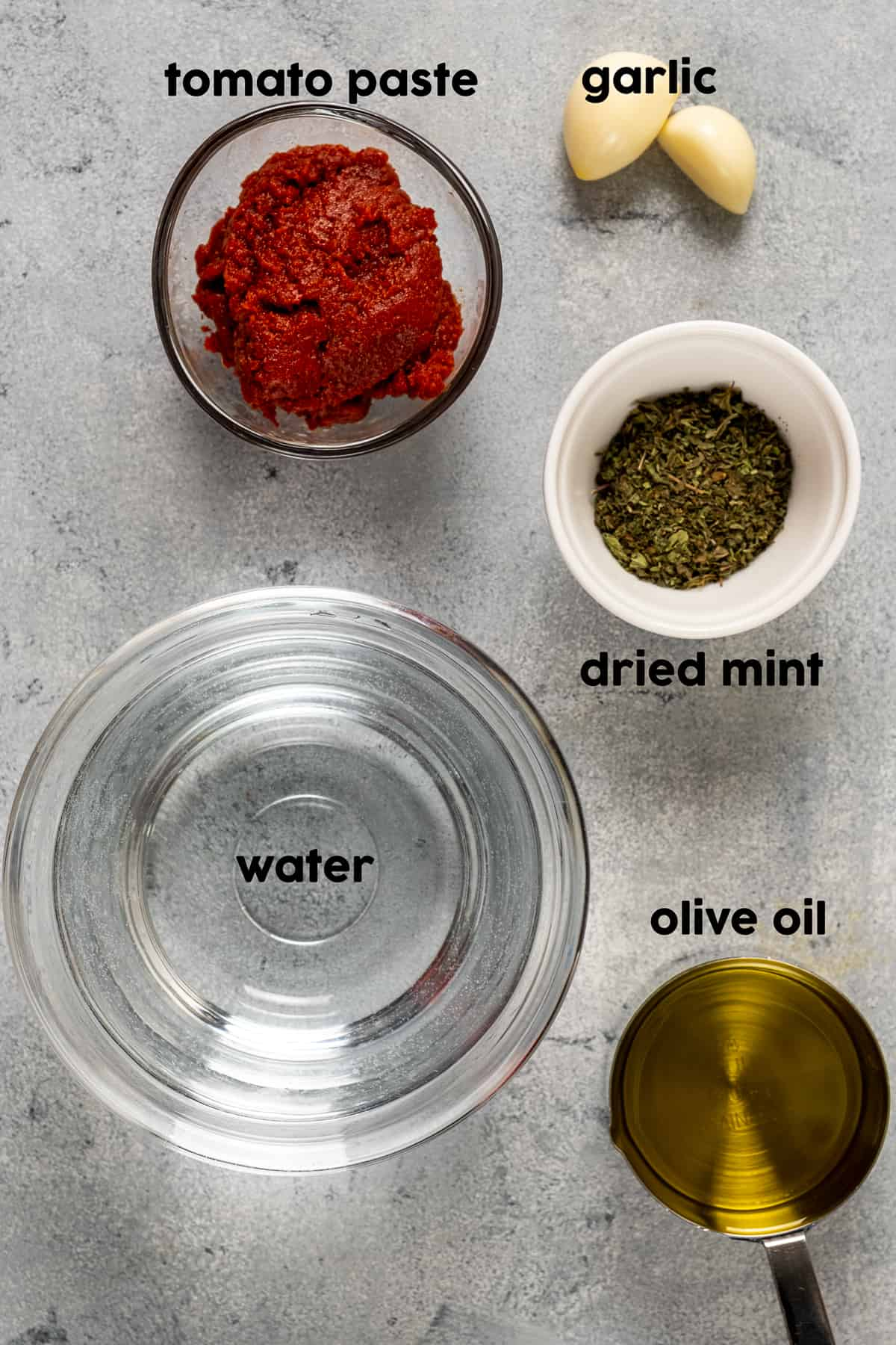 Water, tomato paste, dried mint, garlic and olive oil photographed on a light background.