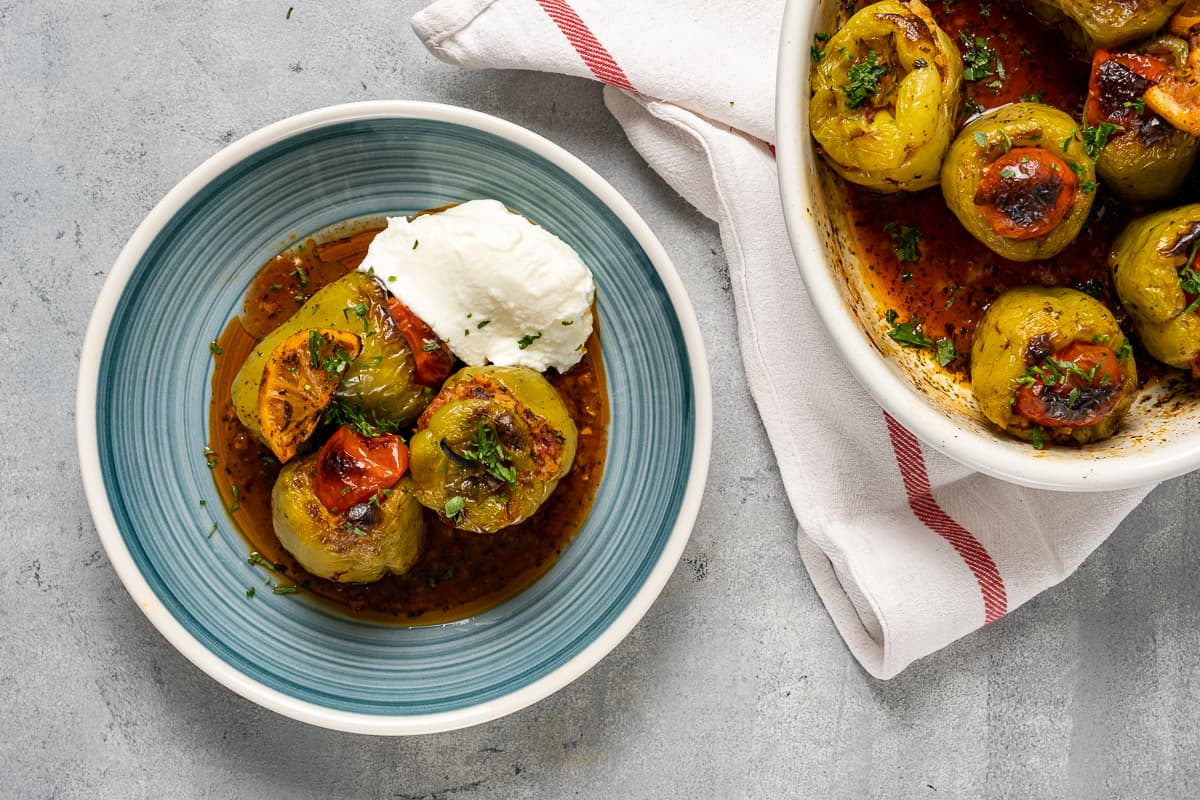Stuffed green peppers served on a bluish plate with its tomato sauce and some yogurt on the side. The baking pan with the remaining dish accompanies.
