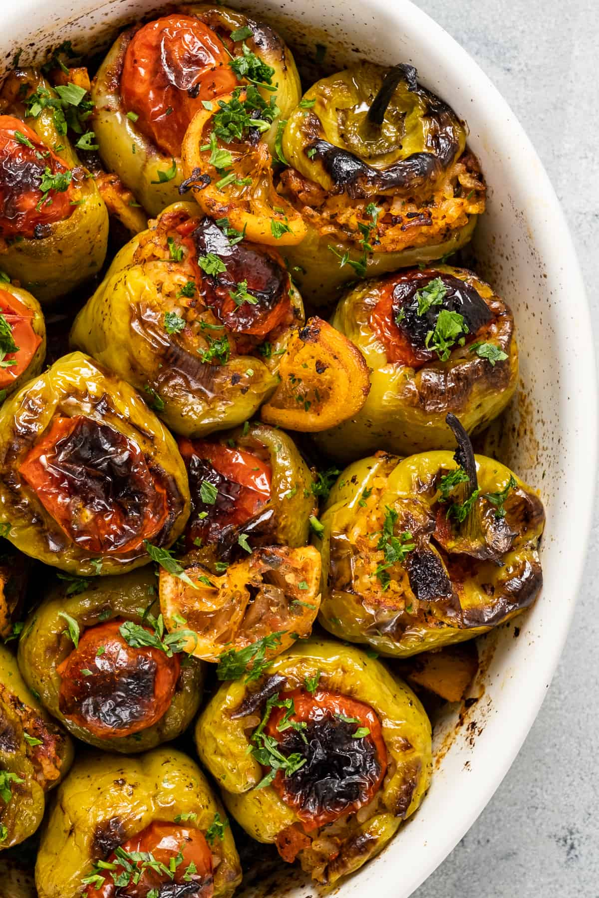 Rice stuffed green peppers topped with tomatoes, lemon slices and chopped parsley in a baking pan.